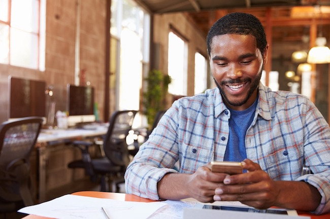 designer-sitting-at-meeting-table-texting-on-mobile-phone-1483512792287